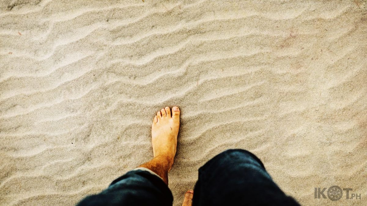 A man in folded blue denim jeans walking through the sand.